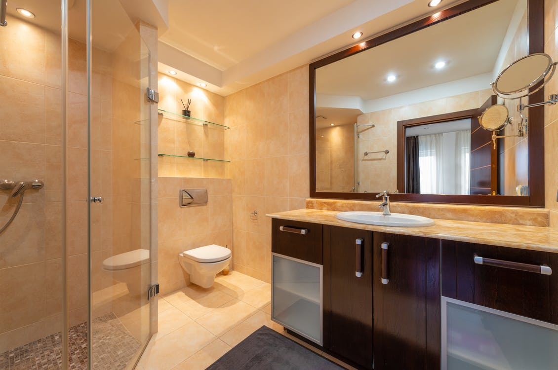 hower room against toilet bowl and cabinet with washbasin under mirrors illuminated