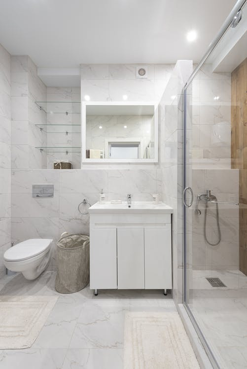 ontemporary bathroom with toilet bowl against cloth basket and wash