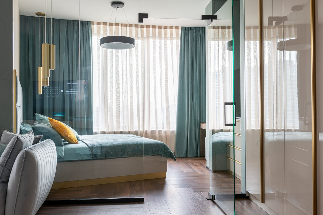 pacious bedroom with glass wall in apartment