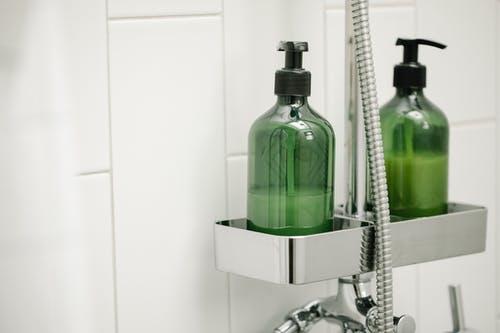 reen dispensers on shelf on shower system
