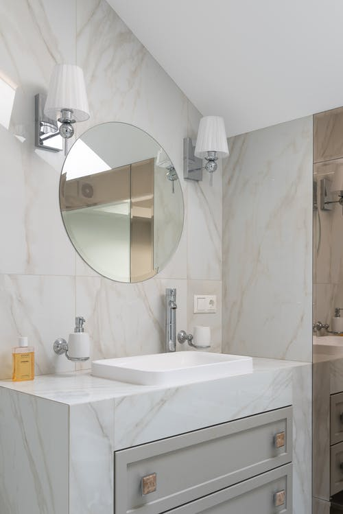odern light bathroom with marble cupboard with sink and mirror hanging on til