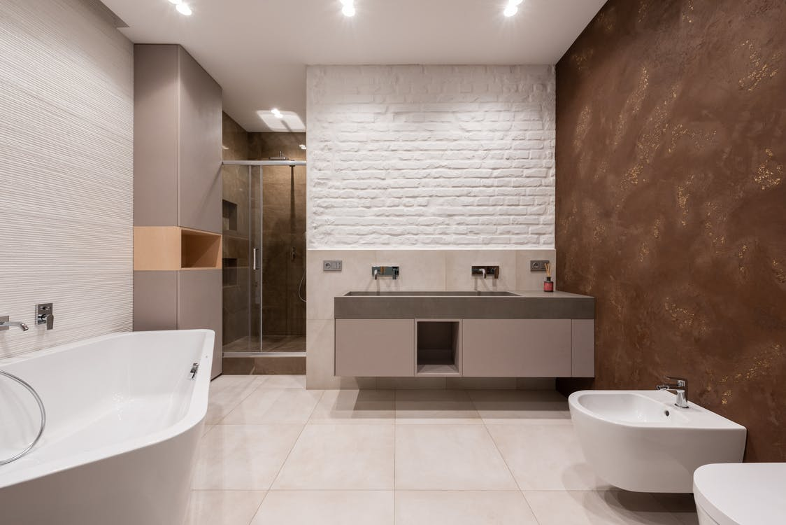 nterior of modern light bathroom with bidet and toilet in front of bath a